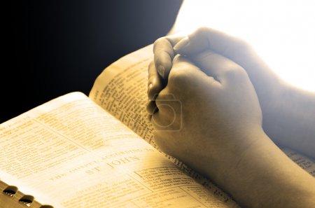 Hände beten auf der Bibel