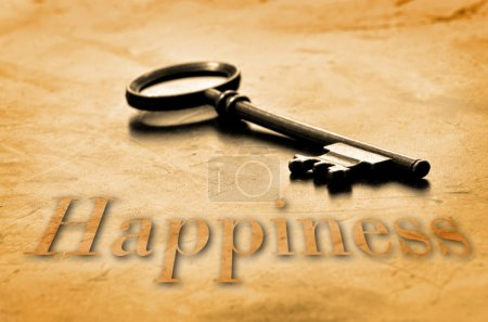 Photo for Key to Happiness on an old worn wooden desk top - Royalty Free Image