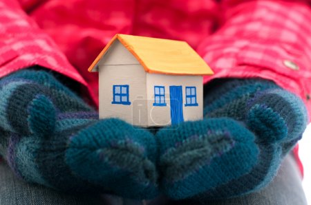 House holds woman in winter gloves