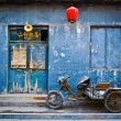 Motorbike cart parked in front of the decaying blue facade of an abandoned shop in Pingyao, China