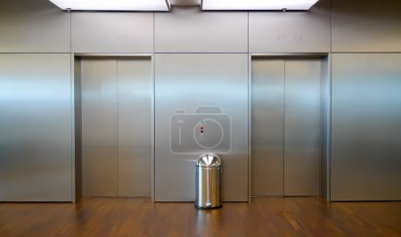 Two brushed metal elevator doors in a minimalistic...
