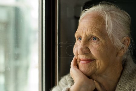 Photo for Lovely grandmother looking in a window, in a train - Royalty Free Image