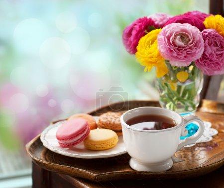 Photo pour Tasse de café avec des macarons sur une table avec des renoncules fleurs - image libre de droit