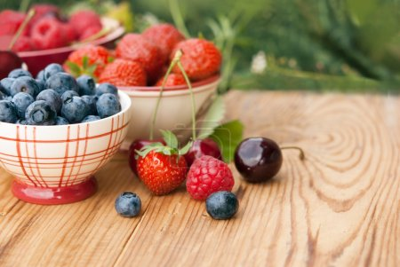 Photo for Berries in bowls on wooden table, fruits, cherry, raspberry, strawberry and bluberry - Royalty Free Image