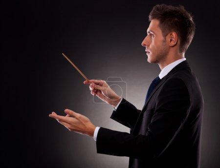 Photo pour Vue latérale d'un jeune homme d'affaires mettant en scène avec un bâton de chef d'orchestre - image libre de droit