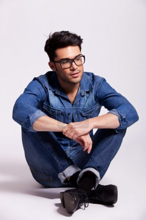 man wearing jeans shirt and glasses, sitting