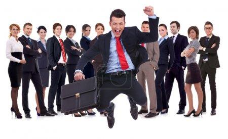 Photo pour Homme d'affaires détenant serviette sauter avec son équipe de l'entreprise formée de jeunes entrepreneurs et entrepreneuses, debout sur un fond blanc - image libre de droit