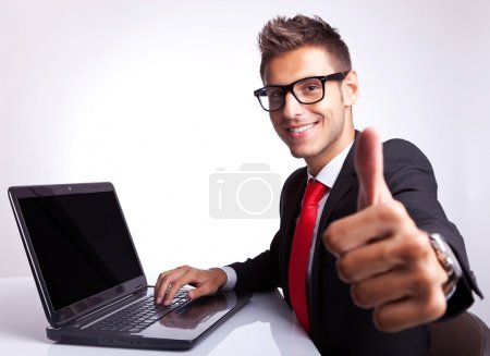 Photo for Side view of a business man working on laptop and making the ok gesture - Royalty Free Image