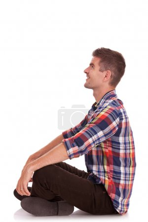 young man sitting with hands on knees