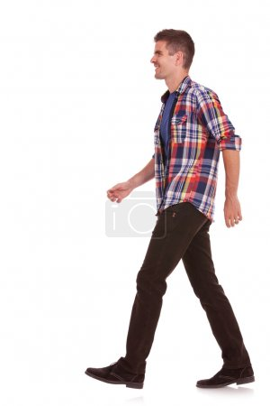 Photo for Side view of a young casual man walking on a white background - Royalty Free Image