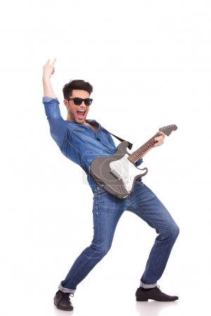 Photo pour Jeune homme décontracté sur une guitare électrique et des cris, fond blanc - image libre de droit