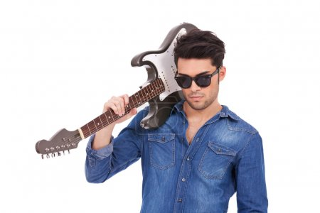 Photo pour Portrait de la découpe d'un jeune homme décontracté avec sa guitare électrique sur son épaule, regardant avec arrogance dans la caméra - image libre de droit