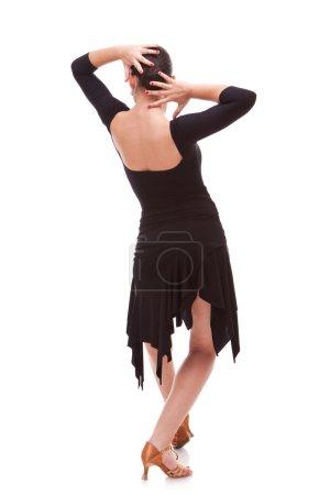 Photo pour Vue arrière d'une jeune femme danseuse de salsa tenant ses mains sur le dos de sa tête, dans une pose de danse - image libre de droit