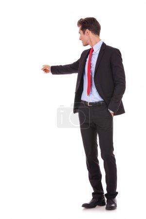 Photo pour Homme d'affaires jeune pointant à quelque chose à son dos sur fond blanc - image libre de droit