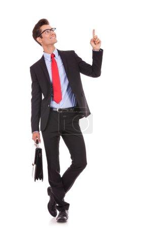 Photo pour Homme d'affaires jeune beau happy smile doigt pointé jusqu'à l'espace copie vide, tout en tenant une mallette - image libre de droit