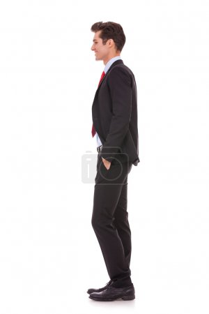 Photo for Stock photo of the side view profile of a well dressed business man smiling. Full length, isolated white. - Royalty Free Image