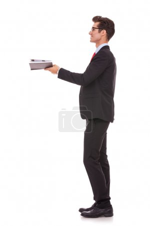 Photo pour Vue latérale d'un homme d'affaires ou un étudiant en regardant quelque chose d'imaginaire qui sort son livre - image libre de droit