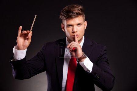 Photo pour Jeune homme d'affaires se faisant passer pour un chef d'orchestre qui fait silence avec son doigt sur ses lèvres, sur fond sombre - image libre de droit