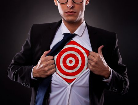 Photo for Young business man showing a target under his shirt on dark background - Royalty Free Image