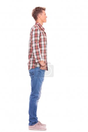 Photo for Side view of a young casual man standing with his hand in his pockets, looking away from the camera - Royalty Free Image