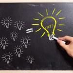 Business man drawing many small light bulbs equal ...