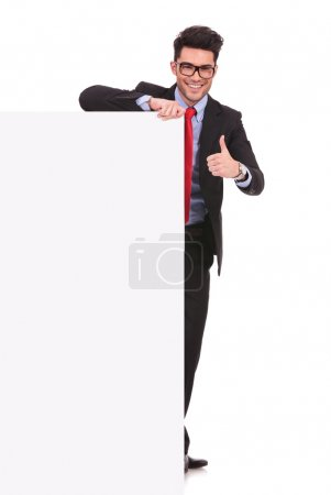 Photo pour Image pleine longueur d'un jeune homme d'affaires tenant un tableau blanc et montrant pouce vers le haut signe tout en souriant à la caméra sur fond blanc - image libre de droit