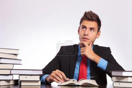 Photo pour Jeune homme d'affaires assis au bureau et lisant avec un regard contemplatif sur son visage - image libre de droit
