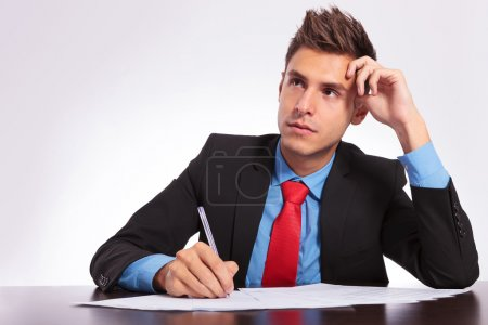 Photo for Young business man sitting at the table thinking what to write - Royalty Free Image