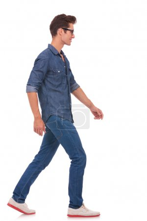 Photo for Side view of a casual young man walking and looking forward, away from the camera. isolated on a white background - Royalty Free Image