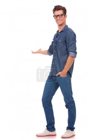 Photo for Full body picture of a young casual man presenting - Royalty Free Image