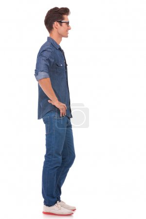 Photo for Side view of a casual young man standing with his hands on his hips and looking away from the camera. isolated on a white background - Royalty Free Image