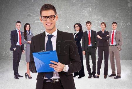 Führungspersönlichkeit hält Klemmbrett mit Business-Team im Rücken