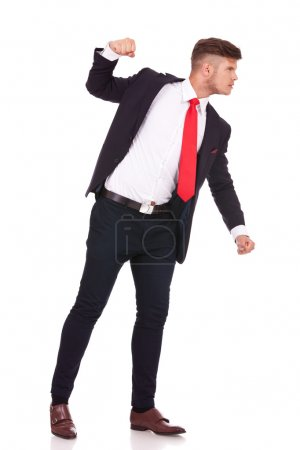 Photo for Side view of a young business man threatening to punch someone. isolated on white background - Royalty Free Image