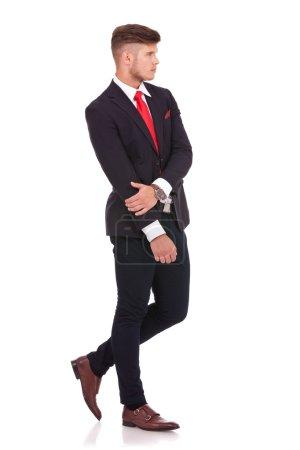 Photo pour Image pleine longueur d'un jeune homme d'affaires tenant un bras avec l'autre et regardant loin de la caméra. isolé sur fond blanc - image libre de droit