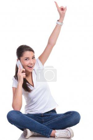 Photo pour Casual jeune femme assise avec les jambes croisées et parler au téléphone tout en pointant vers le haut et en regardant la caméra avec un sourire. isolé sur fond blanc - image libre de droit