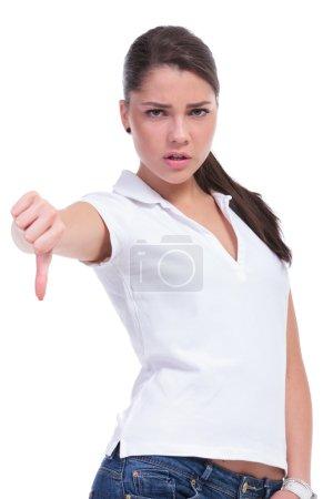 Photo pour Casual jeune femme montrant le pouce vers le bas de geste tout en regardant la caméra. isolé sur fond blanc - image libre de droit