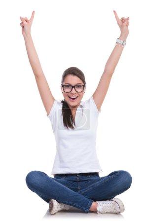 Photo pour Jeune femme occasionnelle assise avec les jambes croisées et acclamant avec les deux index pointant vers le haut tout en souriant à la caméra. isolé sur fond blanc - image libre de droit