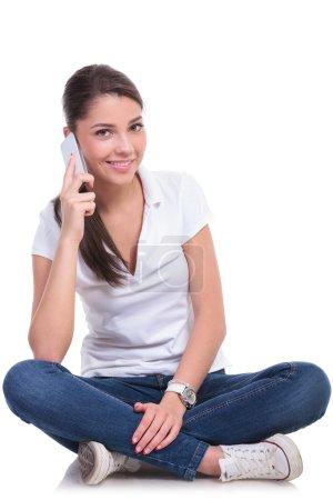 Photo pour Casual jeune femme assise avec les jambes croisées et parler au téléphone tout en souriant à la caméra. isolé sur fond blanc - image libre de droit