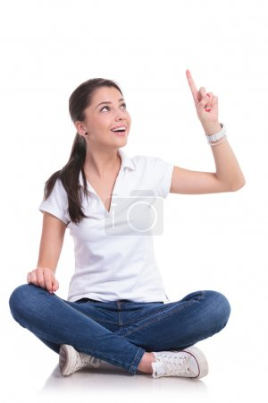 Casual woman sits & points up