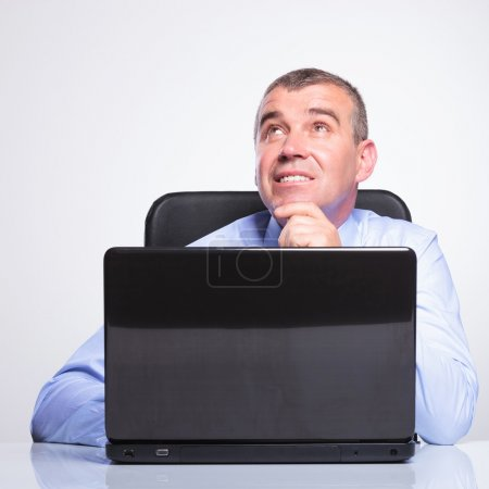 Old business man daydreaming at laptop