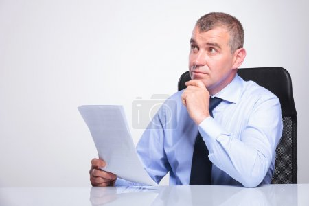 Photo for Senior bussines man sitting pensive at his desk with some documents in his hands, looking away from the camera. on gray background - Royalty Free Image