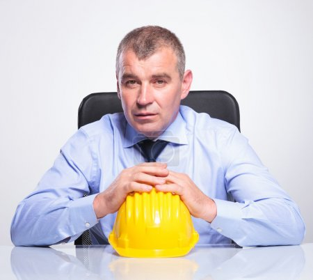 old business man sits with hands on helmet