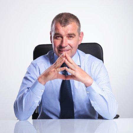 old business man at desk with hands together
