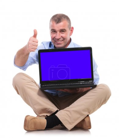 casual old man sits, holds laptop and ok sign