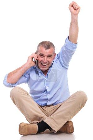 Photo pour Casual homme senior assis sur le sol, les jambes croisées et les acclamations tout en parlant au téléphone et en regardant la caméra. isolé sur fond blanc - image libre de droit
