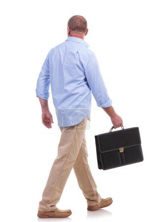 Photo pour Photo pleine longueur d'un aîné occasionnel s'éloignant de la caméra avec une valise à la main. isolé sur fond blanc - image libre de droit