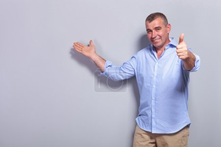casual old man presents and shows ok sign