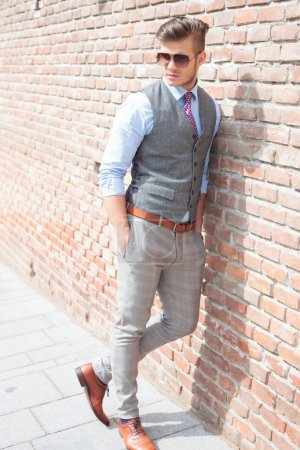 Casual man leans on a brick wall