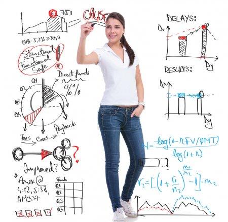 Photo pour Photo de toute la longueur d'une jeune femme casual, écrivant des calculs et des graphiques tout en maintenant son autre main dans la poche. isolé sur fond blanc - image libre de droit