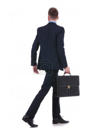 back of a business man with suitcase walking away